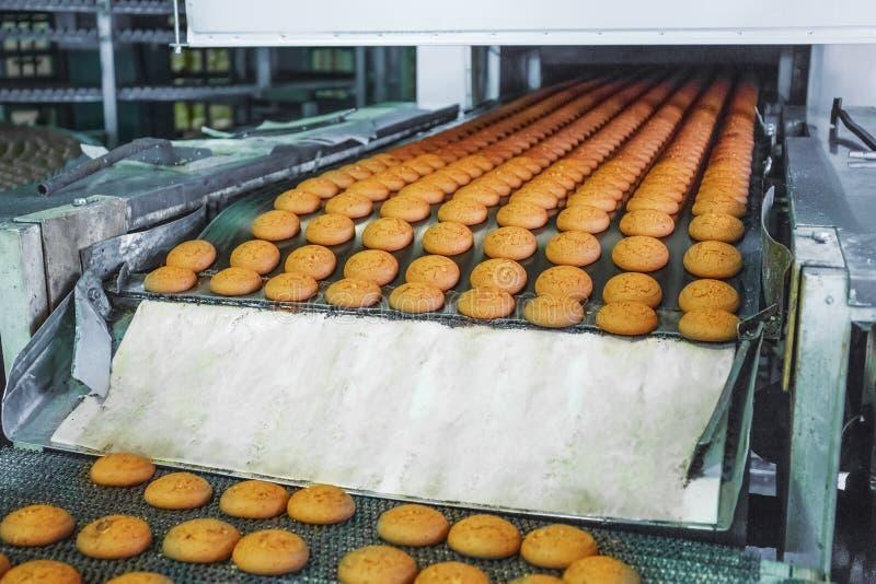 Nahrungsmittelfabrik, industrielles Förderband oder Linie mit Prozess der Vorbereitung der süßen Plätzchen, der Bäckerei und des  lizenzfreie stockfotos