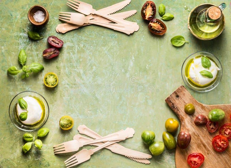 Nahrungsmittelhintergrund mit bunten Tomaten, Mozzarella, Basilikum und Olivenöl Mittelmeerbestandteile Draufsicht mit Kopienraum lizenzfreie stockfotografie