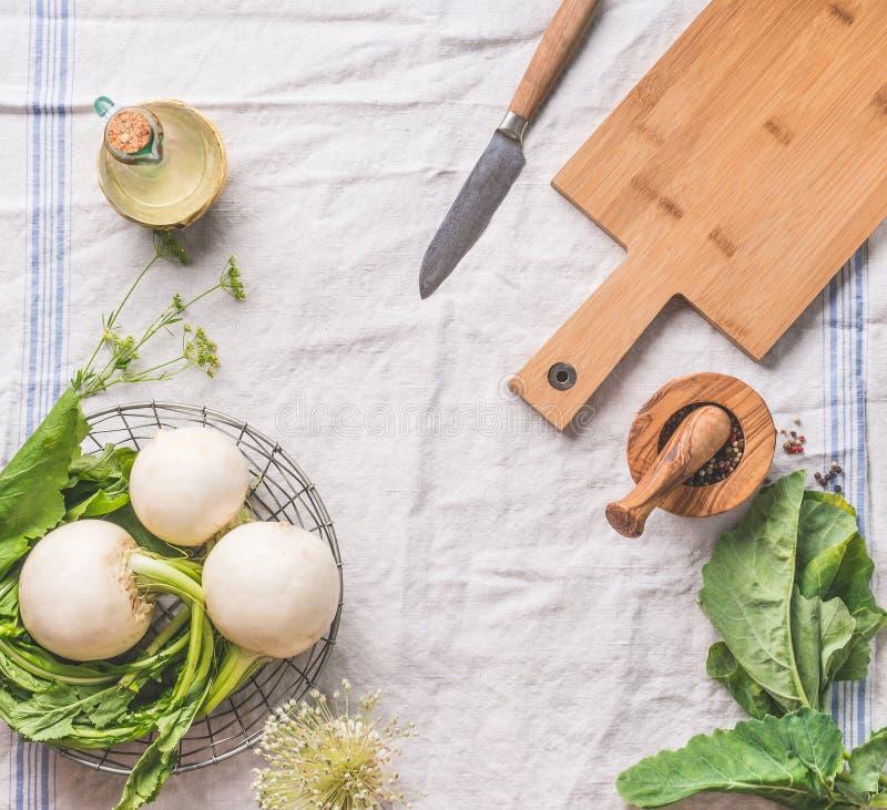 Nahrungsmittelhintergrund mit roher junger Rübe mit Grüns auf hellem Küchentisch mit Schneidebrett und Messer, Draufsicht Gesund stockfoto