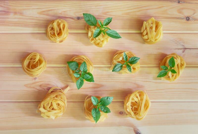 Nahrungsmittelmuster gemacht von den Bandnudelnteigwaren mit grünen Basilikumblättern lizenzfreie stockfotos