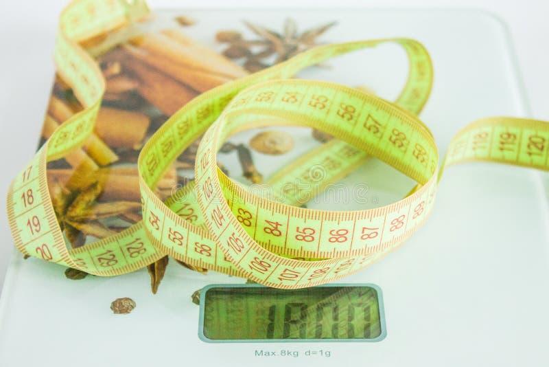 Nahrungsmittelskalen und messendes Band auf weißem Hintergrund lizenzfreie stockfotos