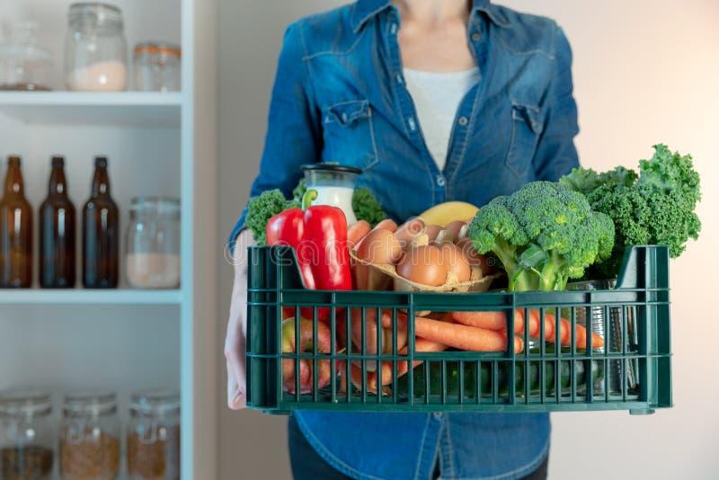 Nahrungsmittelzustelldienst - Frau mit Lebensmittelgesch?ftkasten auf grauem Hintergrund stockbild