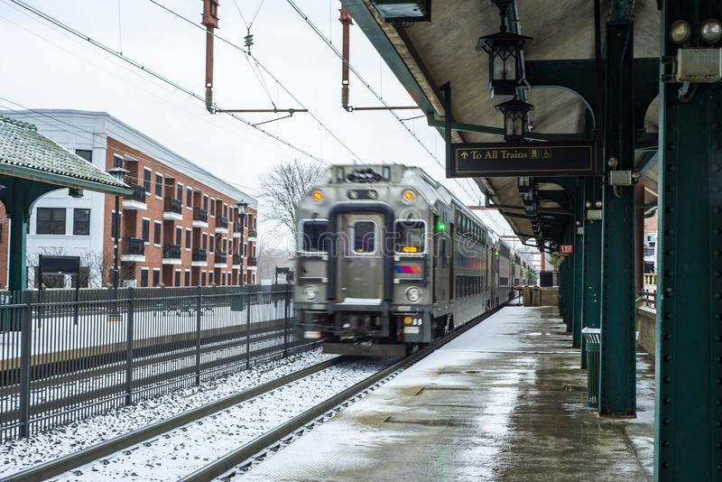 Nahverkehrszug, der Bahnhof nach Schnee verlässt stockfotografie