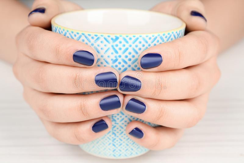 Nail art concept. Beautiful female hands with neat manicure holding cup. Closeup royalty free stock photography