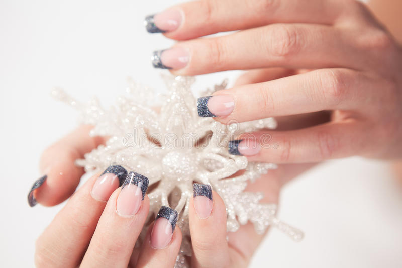 Nail art design. Winter nail art design. Woman hands with snowflake on white background royalty free stock photo