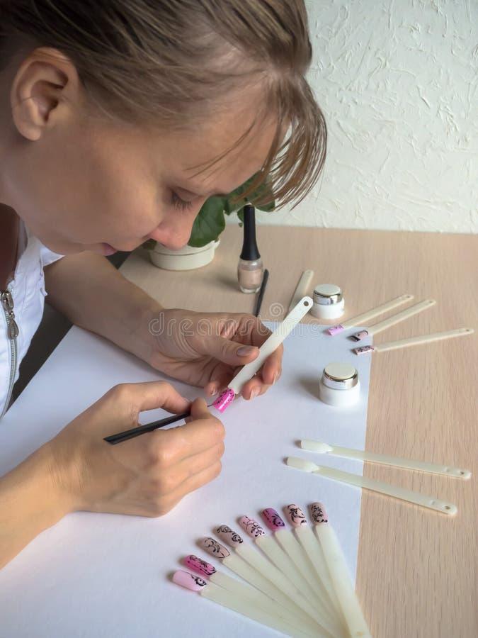 Nail art design. Female master draws on tips. stock photos