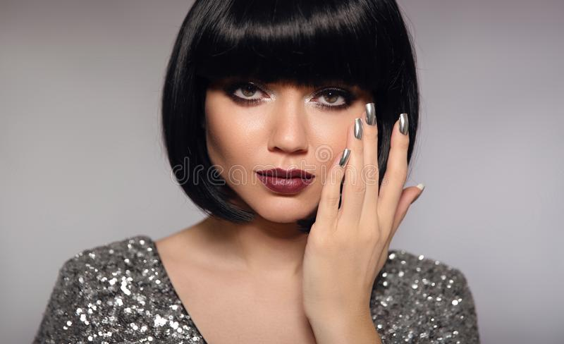 Nail art polish manicure. Short bob hair woman model. Fashion br. Unette close up portrait with beauty makeup and silver manicured nails isolated on gray royalty free stock images