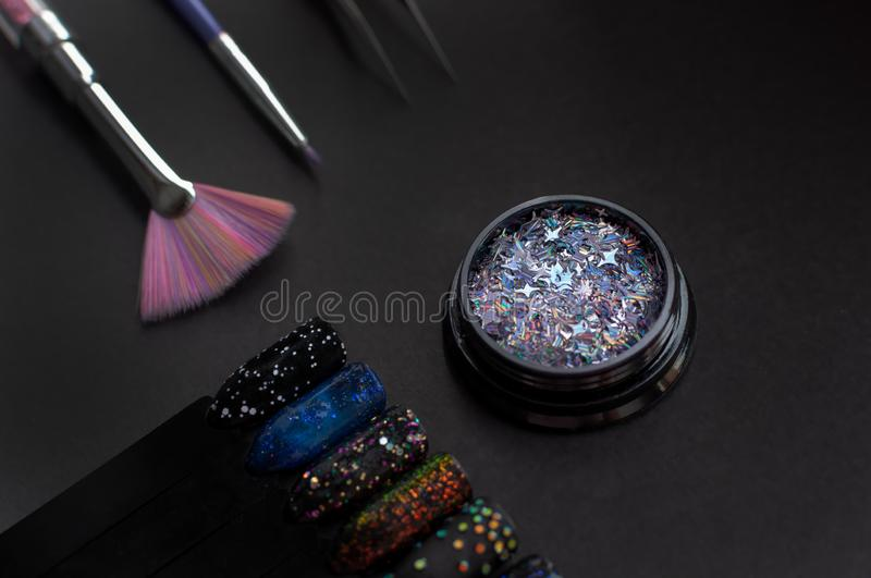 Nail art samples and accessories on black background. Black nail tips with glitter and starry night sky nail art. Top stock photo