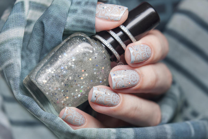 Nail art with silver glitter and gray design. stock photography