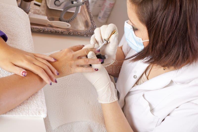 Nail Designer Finishing Acrylic Fingernails Royalty Free Stock Images