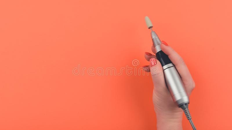 Nail Drill Machine Pen in women hand on coral background. Hardware hybrid manicure, nail care flat lay with copy space stock photo