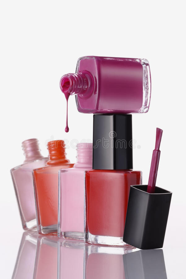 Nail Enamel. Five nail enamels, one with cap off and enamel spilling out stock image