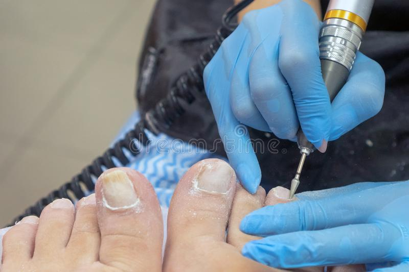 Pedicure process. Pedicure makes the apparatus. Torn glove royalty free stock photo