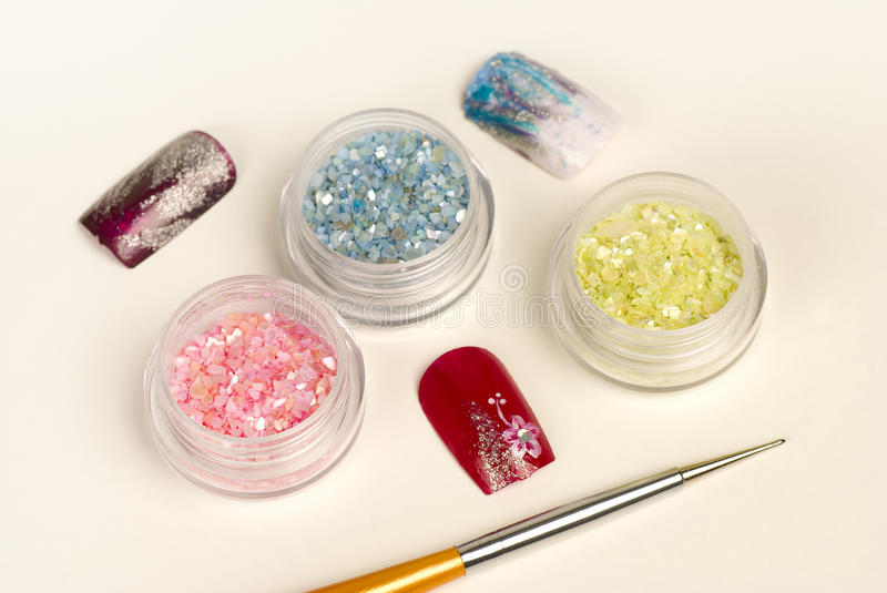 Nail glitter. Some finished samples, utensils and boxes with glitter stock photo