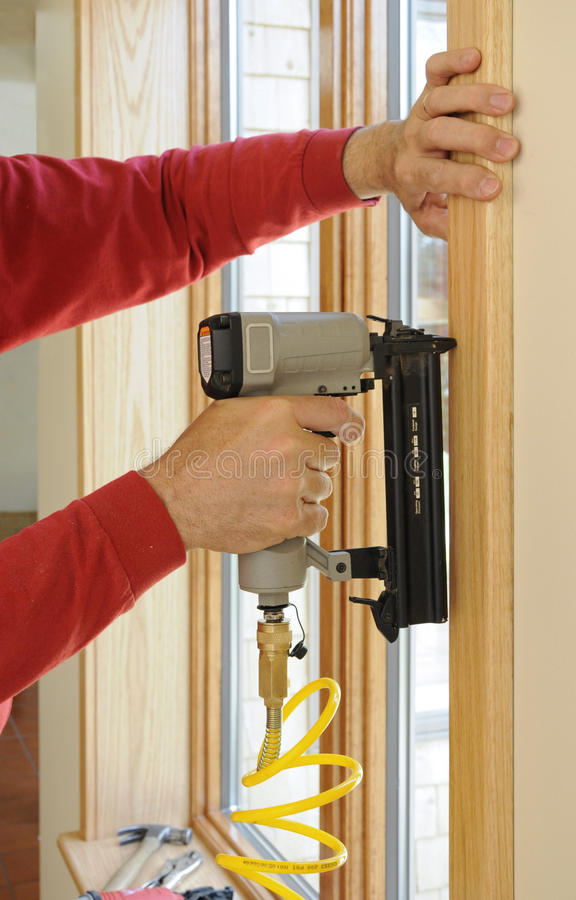 Nail gun being used to install wood trim around wi. Ndows with finishing nails royalty free stock images