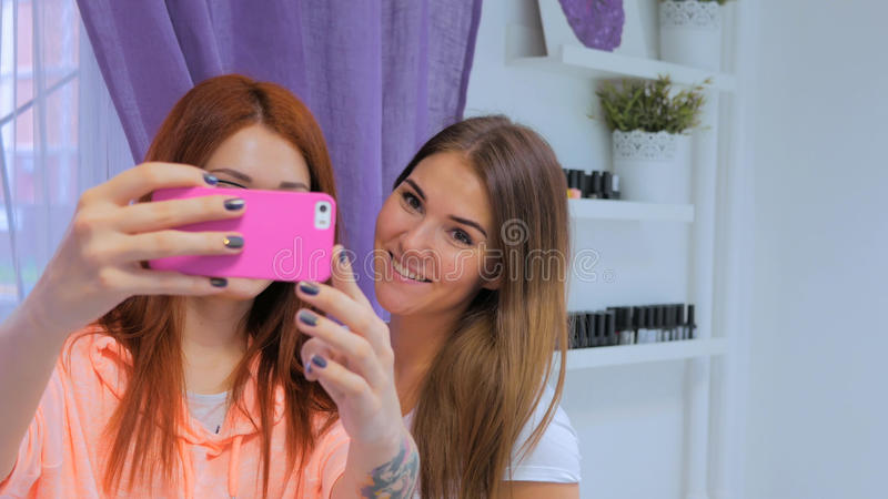Nail master and her client taking selfie at salon. Beauty, fashion and technology concept stock image