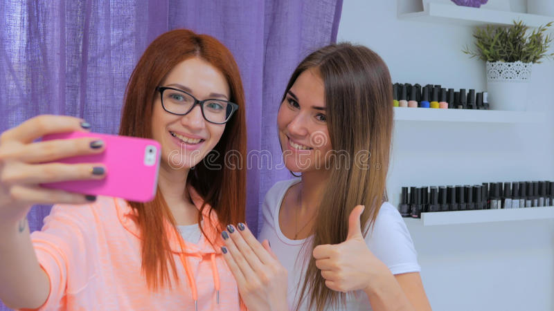 Nail master and her client taking selfie at salon. Beauty, fashion and technology concept stock photo