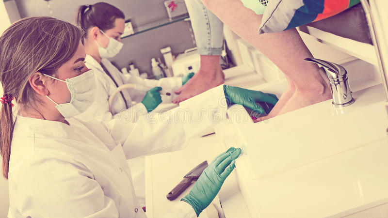 Nail pedicure technician performing procedure royalty free stock photography