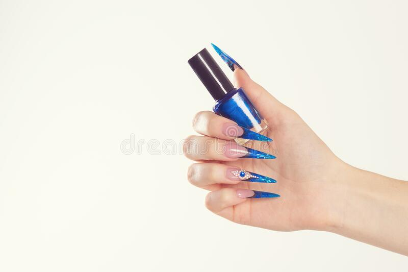 Nail Polish. Art Manicure. Modern style blue Nail Polish. Beauty hands holding blue bottle. Stylish Colorful stiletto Nails. Isolated white background stock images