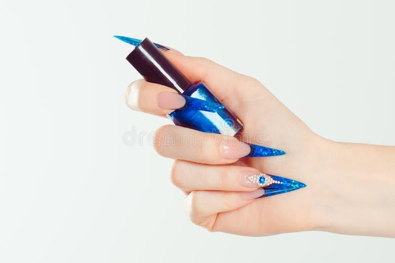 Nail Polish. Art Manicure. Modern style blue Nail Polish. Beauty hands holding blue bottle. Stylish Colorful stiletto Nails. Isolated white background royalty free stock photo
