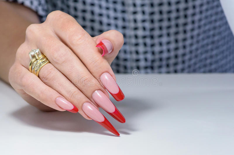 Nail Polish. Art Manicure. Modern style red black gradient Nail Polish. Beauty hands with Stylish Colorful trendy Nails w. Hite background stock images