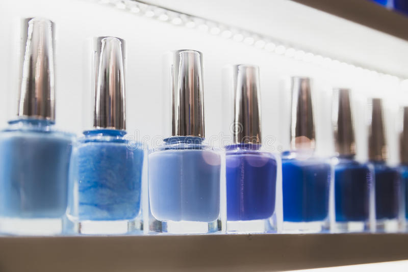 Nail polish collar color lakes. Set of different nail varnishes on shelves in cosmetic store royalty free stock photos