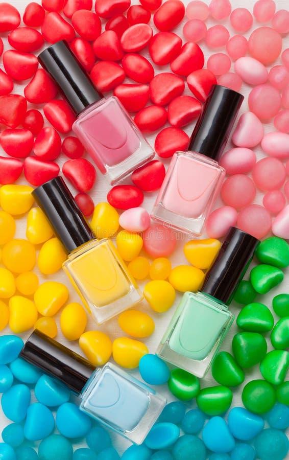 Pastel colors nail polish. Beauty blogger concept. Nail polish of various pastel colors and colorful candies. Mockup or Beauty blogger concept stock photos