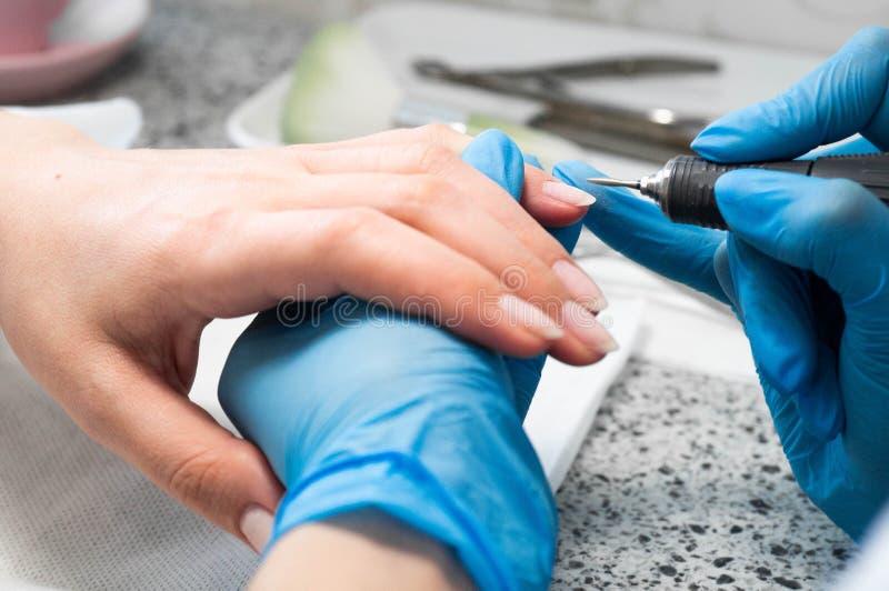 Nail technician giving a customer a manicure at nail salon. Young caucasian woman receiving a manicure. Closeup shot of a woman doing manicure stock photo