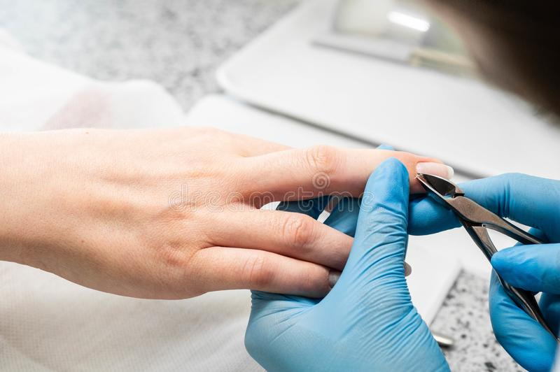 Nail technician giving a customer a manicure at nail salon. Young caucasian woman receiving a manicure. Closeup shot of a woman doing manicure royalty free stock image