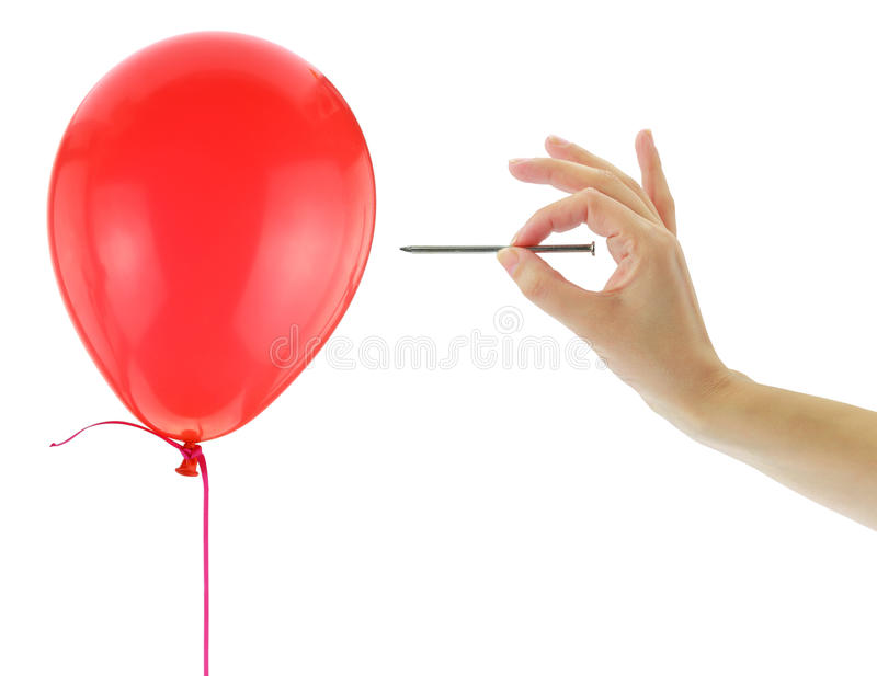Nail about to pop a balloon. Isolated on white royalty free stock photo