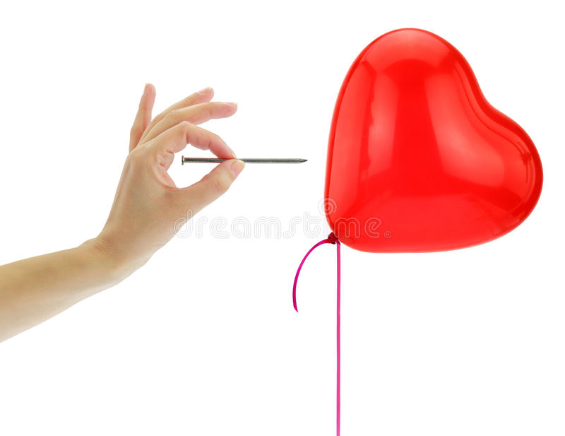 Nail about to pop a heart balloon. Isolated on white royalty free stock photography