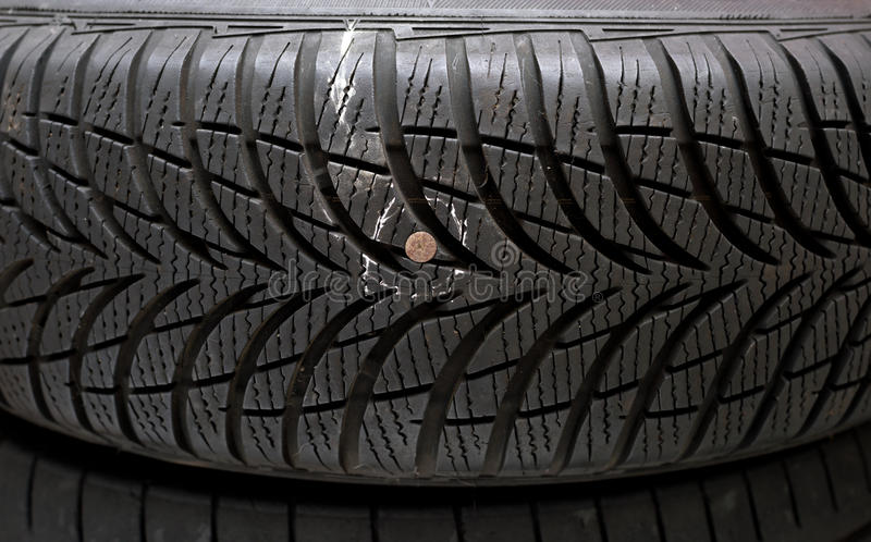 Nail in tyre. Metallic nail in damaged tyre before repair stock image