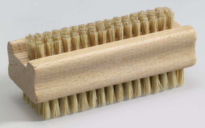 Nailbrush. Wooden nail brush in light grey back royalty free stock image