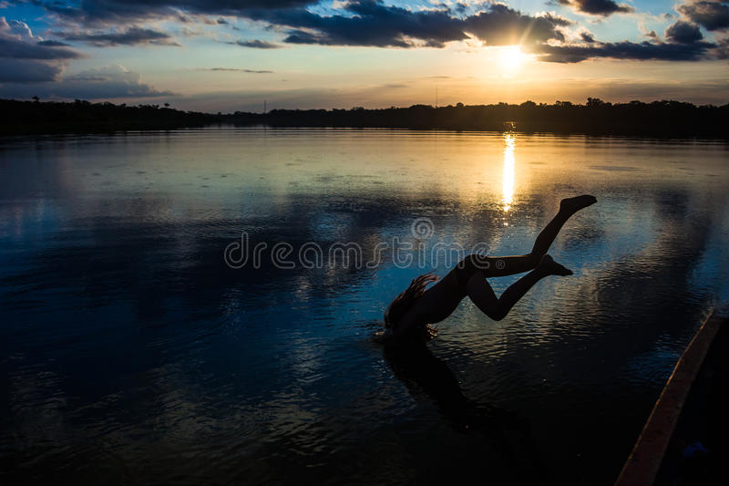 Nailed in the lagoon Limoncocha. Reflection of the sun at sunset in the Limoncocha lagoon in the Ecuadorian Amazon stock photography
