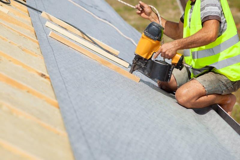 Nailgun automático do uso do trabalhador do construtor do Roofer para unir a membrana do telhado imagem de stock royalty free