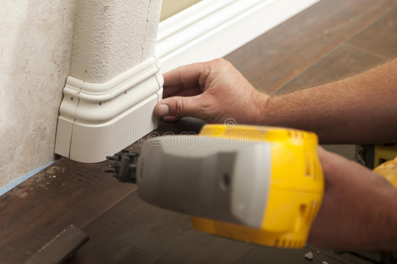 Nailing New Baseboard with Bull Nose Corners and New Laminate Fl. Contractor Nailing New Baseboard with Bull Nose Corners and New Laminate Flooring Renovation royalty free stock photos