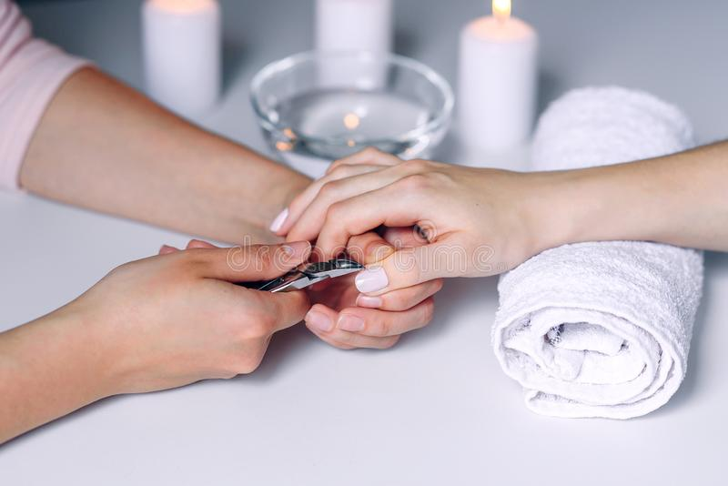Nails beauty. Woman hands receiving nail care treatment by professional manicure specialist in nail salon. Manicurist stock image