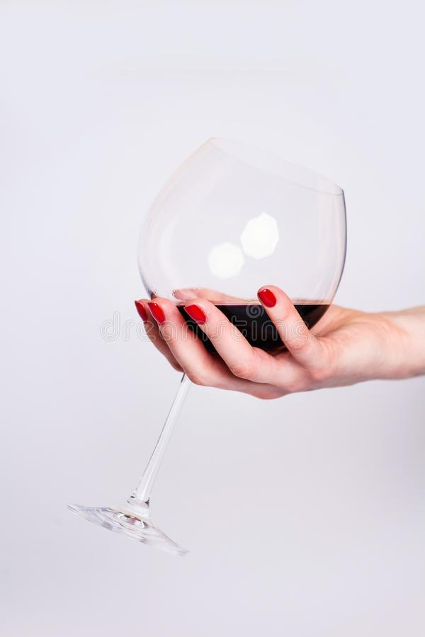 Nails Design. Hands With Bright Red Spring Manicure On Grey Background. Close Up Of Female Hands. Art Nail. Red wine glass royalty free stock photos