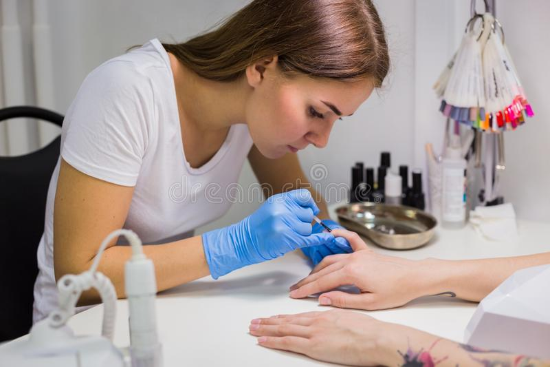 Nails painting with brush in nail salon. On women hands royalty free stock photo