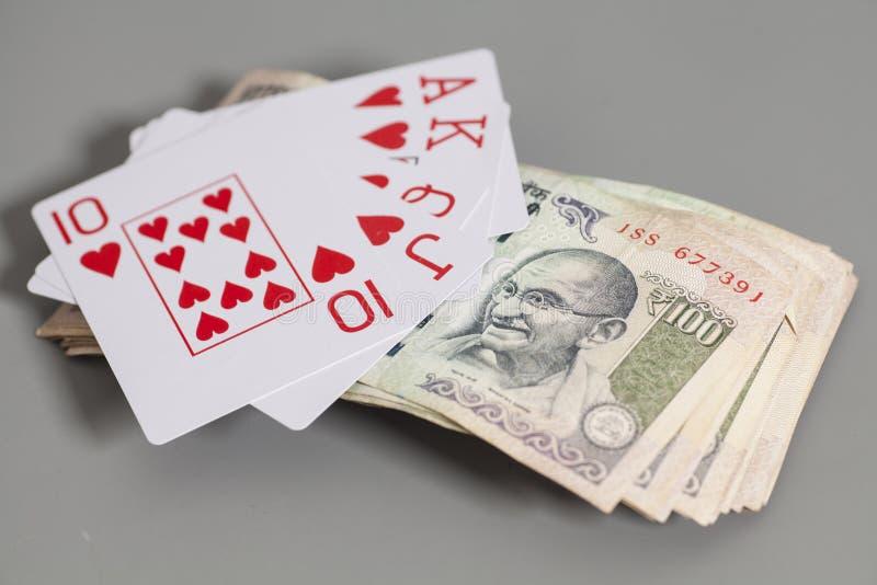 Naipes de la escalera real y billetes de banco indios de la rupia de la moneda fotografía de archivo libre de regalías