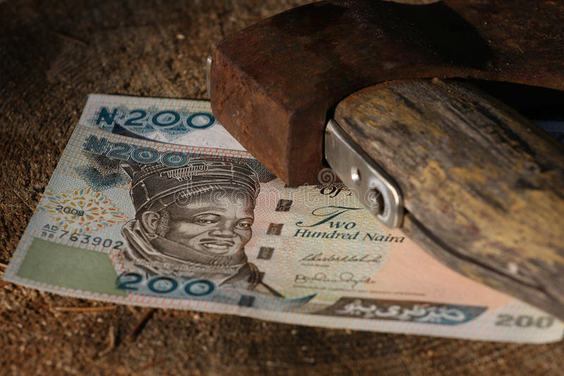 Naira bills under old axe stock photos