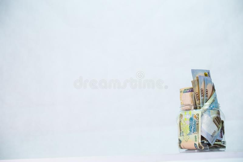 Naira notes in a glass jar - concept of Saving. Local currencies and Naira notes in a glass jar - concept of Saving stock images