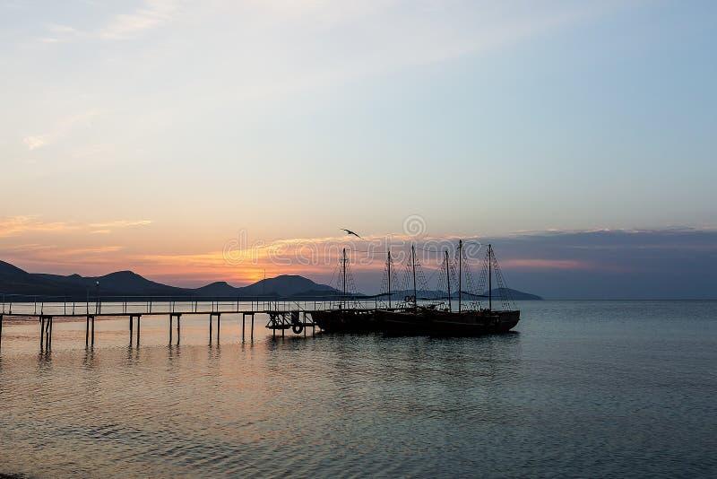 Naissez par la mer avec une jetée et des bateaux photo libre de droits