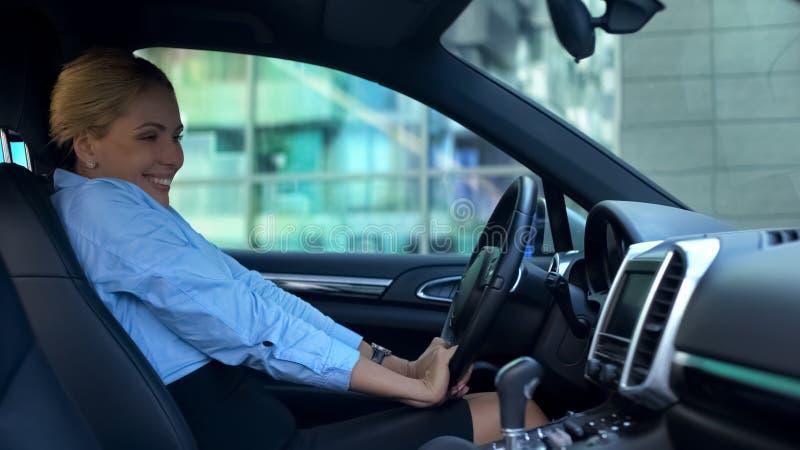 Naiwna blondynka zachwycał z nowym samochodem, wzruszająca kierownica, radosna jako dziecko obraz stock