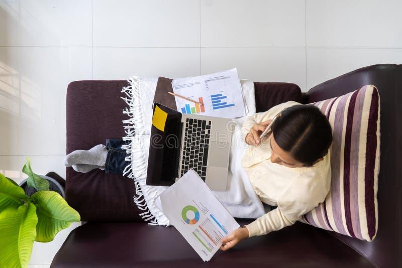 Najlepiej widoczna kobieta pracująca na laptopie z gadającym smartfonem na kanapie w domu zdjęcia stock