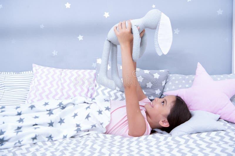 Najlepsi Przyjaciele Dziewczyny dziecko kłaść na łóżku z popielatą królik zabawką w jej sypialni Dzieciak przygotowywa iść łóżko  zdjęcie royalty free