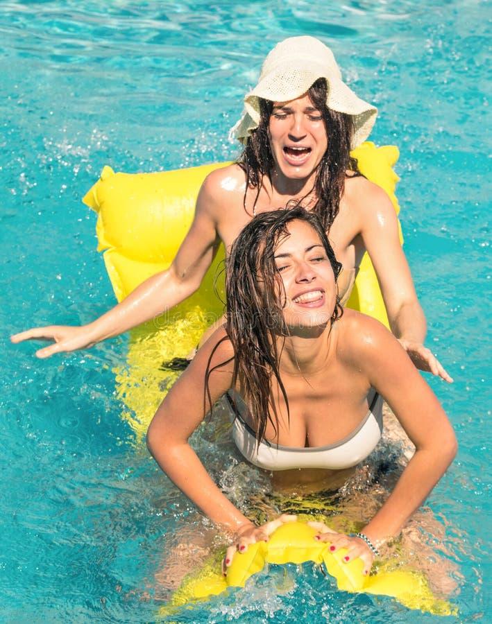 Najlepsi przyjaciele w bikini cieszy się czas wpólnie w pływackim basenie obraz stock