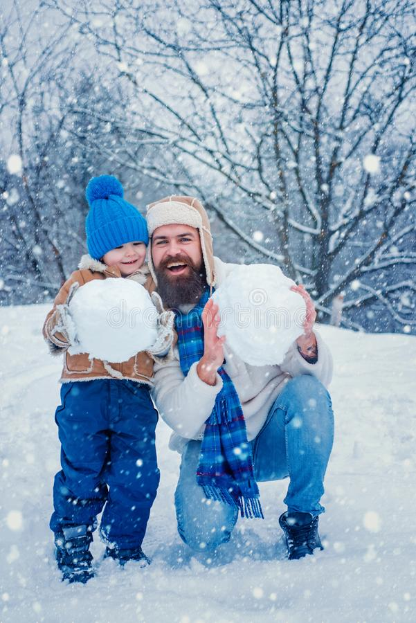 Najlepsza gra zimowa dla szczęśliwej rodziny Szczęśliwy ojciec i syn robią bałwana w śniegu Śnieżny śmieszny śnieg Szczęśliwy fotografia royalty free
