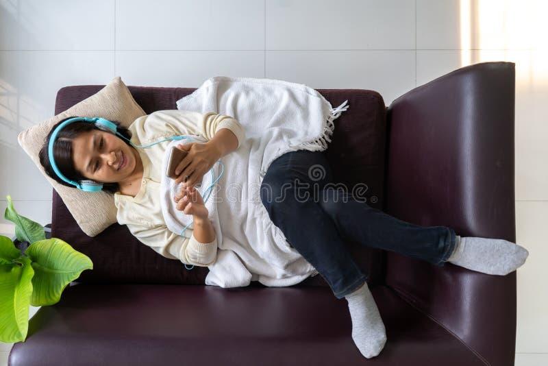 Najlepsze widoki azjatycka kobieta słuchająca muzyki w słuchawkach leżąc na sofie zdjęcia stock