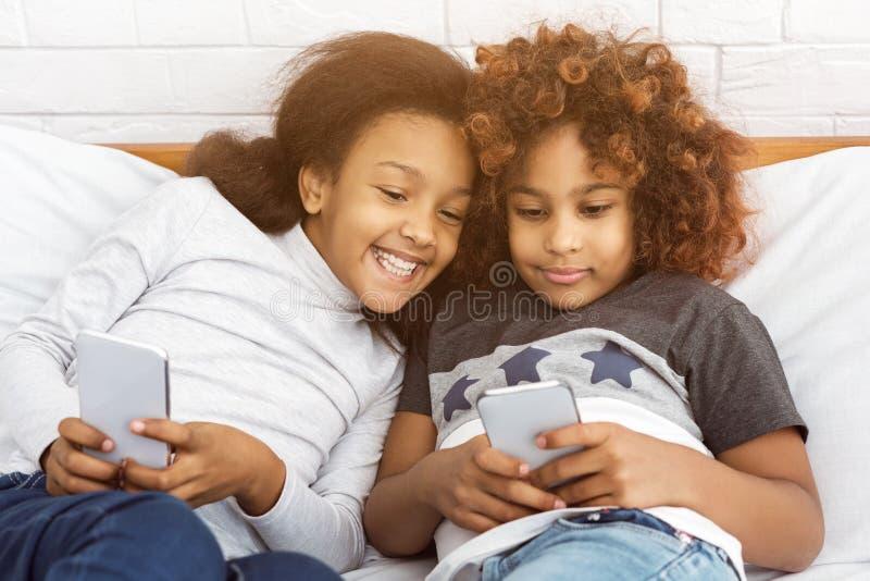 Najlepszy przyjaciele bawić się na telefonach, kłama na łóżku fotografia royalty free